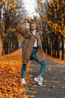 Jovem mulher com um penteado moderno com um casaco elegante posa ao ar livre em um parque