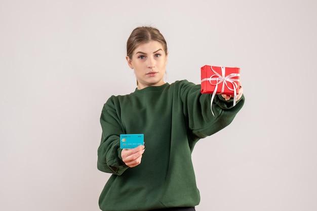 Jovem mulher com um pequeno presente de natal e um cartão de banco