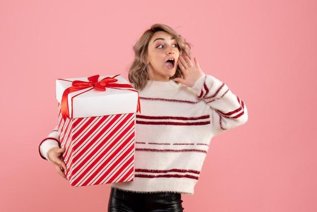 Jovem mulher com um presente de natal de frente
