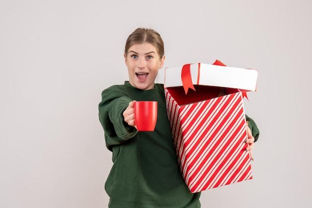 Jovem mulher com um presente de natal e uma xícara de chá de frente