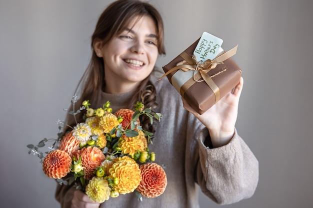 Jovem mulher com um presente para o dia das mães e um buquê de flores nas mãos