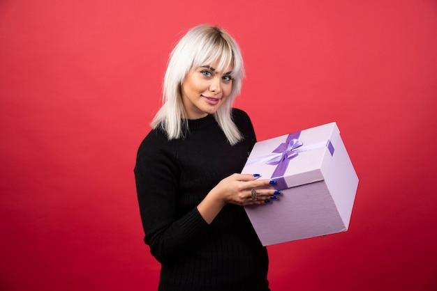 Jovem mulher com um presente sobre um fundo vermelho. foto de alta qualidade