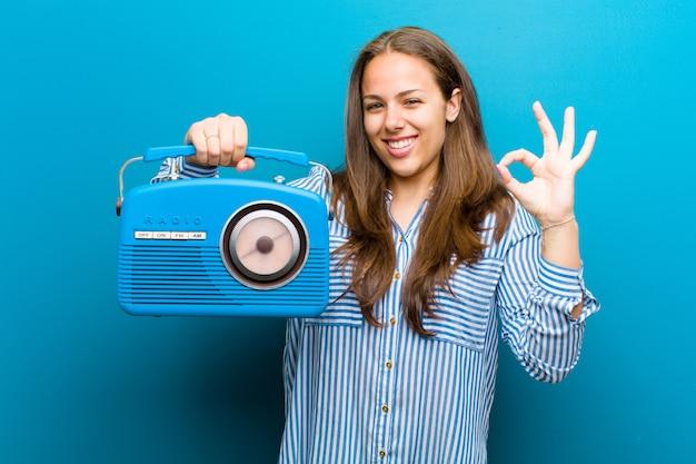 Jovem mulher com um rádio vintage contra azul