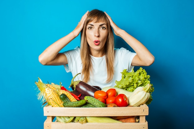 Jovem mulher com um rosto surpreso mantém uma caixa com legumes frescos em azul. bom conceito de colheita, produto natural
