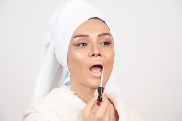 Jovem mulher com um roupão de banho a aplicar um batom