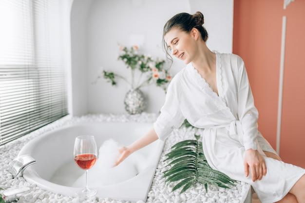 Jovem mulher com um roupão de banho branco, sentada na beira da banheira com espuma. interior do banheiro com janela e vidro com vinho tinto