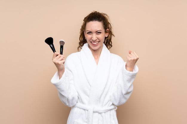 Jovem mulher com um roupão segurando os pincéis de maquiagem comemorando uma vitória