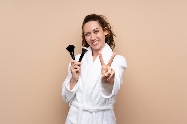 Jovem mulher com um roupão segurando os pincéis de maquiagem, sorrindo e mostrando sinal de vitória