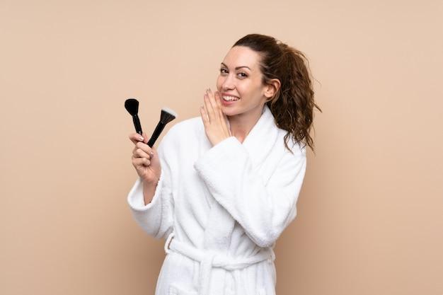 Jovem mulher com um roupão segurando os pincéis de maquiagem sussurrando algo