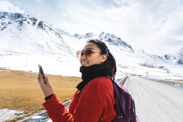 Jovem mulher com um smartphone nas montanhas do himalaia