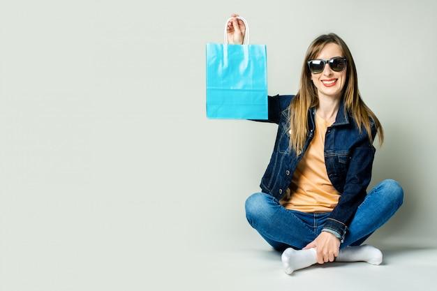 Jovem mulher com um sorriso em uma jaqueta jeans e óculos escuros segura sacolas de compras enquanto está sentado no chão em um espaço claro.