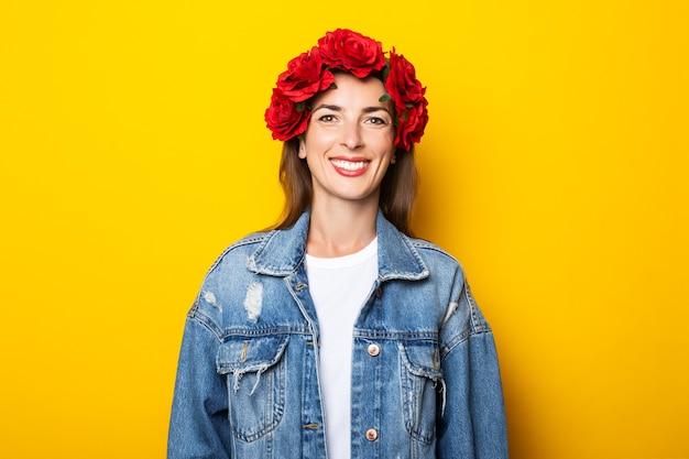 Jovem mulher com um sorriso em uma jaqueta jeans e uma coroa de flores vermelhas na cabeça em uma parede amarela.