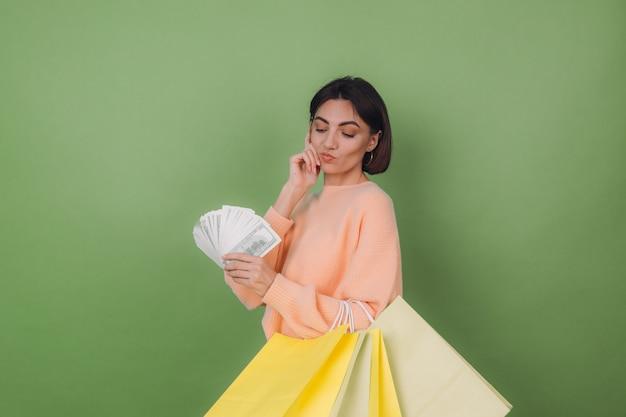 Jovem mulher com um suéter casual cor de pêssego isolado em uma parede verde-oliva segurando um leque de notas de 100 dólares, dinheiro e sacolas de compras, pensando positivo, sorrindo, espaço de cópia