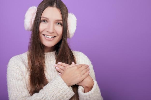Jovem mulher com um suéter e fones de ouvido cruzou as mãos no coração