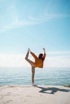 Jovem mulher com um suéter em uma praia praticando ioga pose natarajasana do dançarino