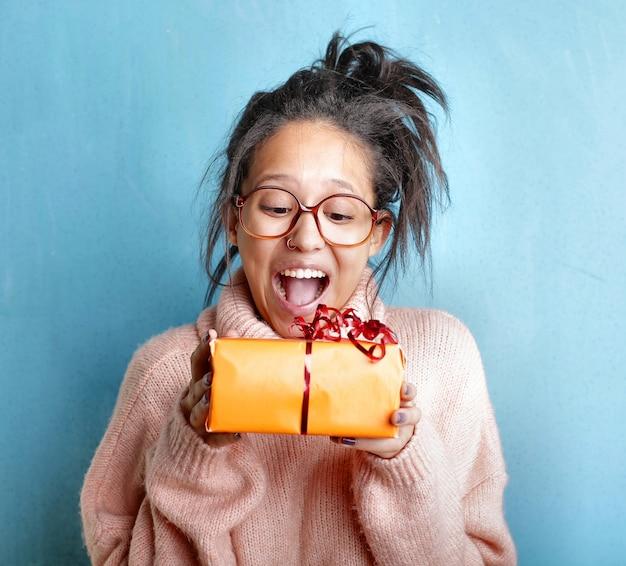 Jovem mulher com um suéter rosa expressando felicidade enquanto segura uma caixa de presente