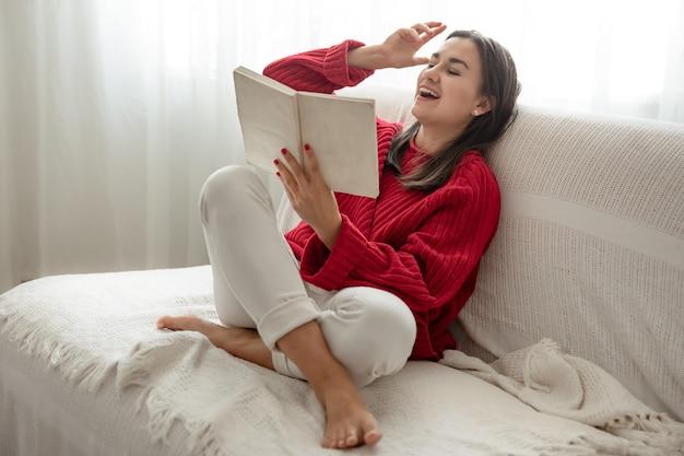 Jovem mulher com um suéter vermelho no sofá em casa com um livro nas mãos.