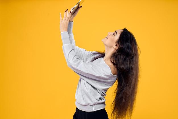 Jovem mulher com um tablet, laptop e fones de ouvido posando em um espaço, emoções diferentes