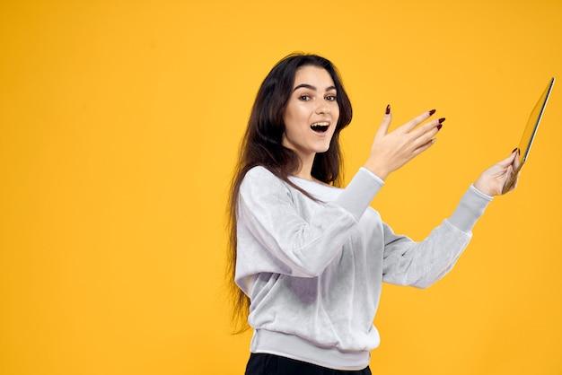 Jovem mulher com um tablet, laptop e fones de ouvido posando em uma parede no estúdio, emoções diferentes