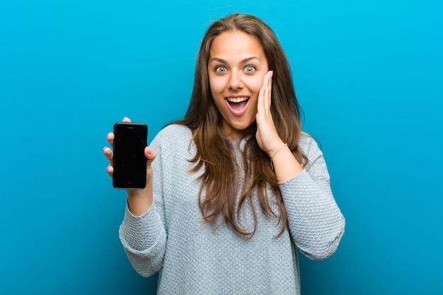 Jovem mulher com um telefone móvel azul