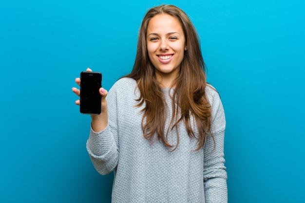 Jovem mulher com um telefone móvel contra o fundo azul