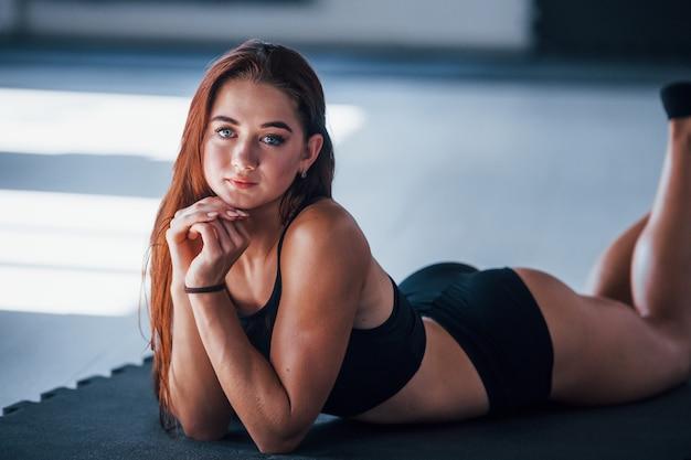 Jovem mulher com um tipo de corpo magro e com roupas esportivas pretas, deitada sobre o tapete de fitness.