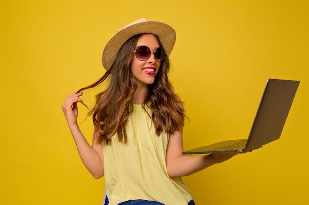 Jovem mulher com um vestido amarelo com chapéu e óculos escuros ouvindo música usando um laptop