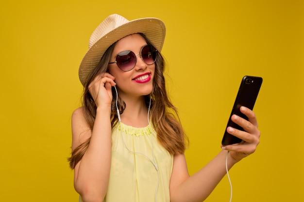 Jovem mulher com um vestido amarelo com chapéu e óculos escuros ouvindo música
