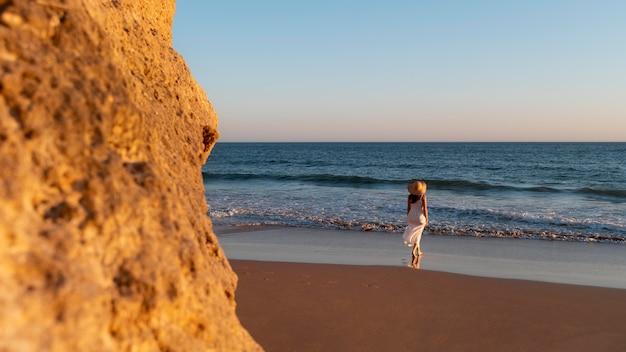 Jovem mulher com um vestido branco junto ao mar