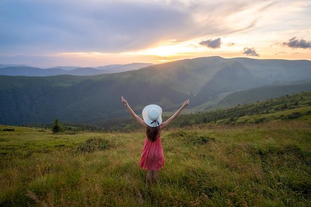 Jovem mulher com um vestido vermelho de pé num prado gramado em uma noite ventosa nas montanhas de outono, levantando as mãos, apreciando a vista da natureza.