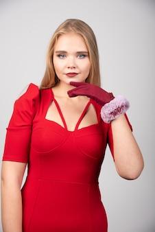 Jovem mulher com um vestido vermelho, olhando para a frente.