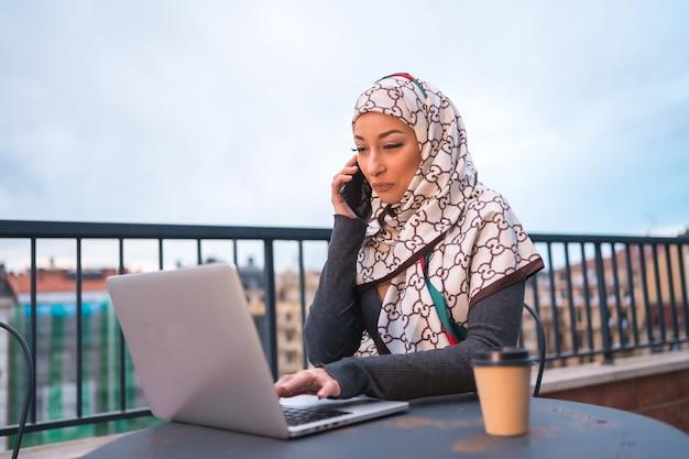 Jovem mulher com um véu branco em frente ao computador na esplanada de uma cafetaria, com o computador e a falar ao telefone. jovem moderno com novas tecnologias