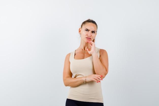 Jovem mulher com uma blusa bege em pose pensativa e pensativa