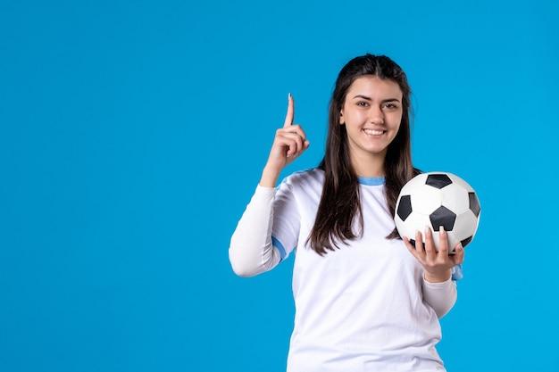 Jovem mulher com uma bola de futebol na parede azul de frente