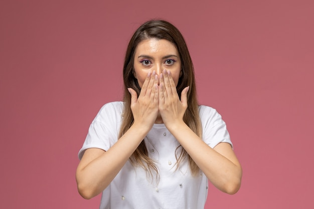 Jovem mulher com uma camisa branca cobrindo a boca de frente