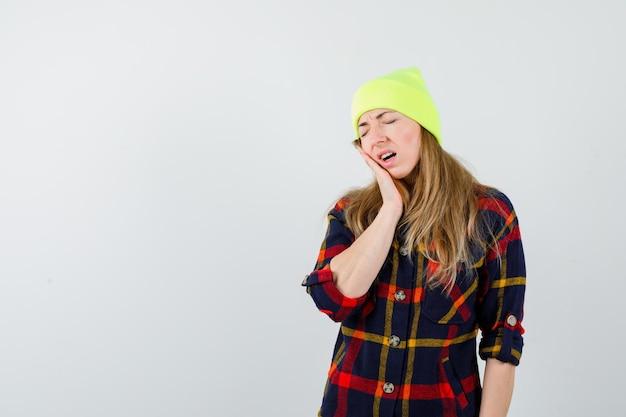 Jovem mulher com uma camisa xadrez e um chapéu