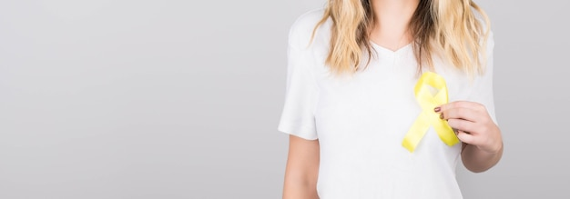 Jovem mulher com uma camiseta branca segurando um símbolo de alerta de fita amarela para suicídio