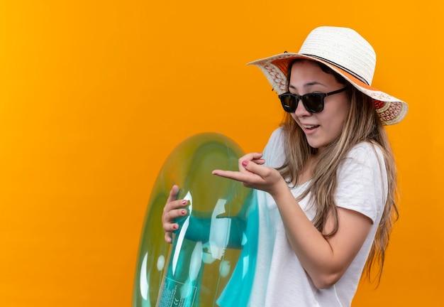 Jovem mulher com uma camiseta branca usando um chapéu de verão segurando um anel inflável, brincando olhando para o lado apontando com o dedo indicador para algo em pé sobre a parede laranja