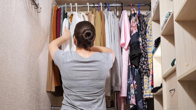 Jovem mulher com uma camiseta cinza com coque no cabelo escolhe roupas penduradas na barra de metal em um closet contemporâneo em casa, perto da vista traseira