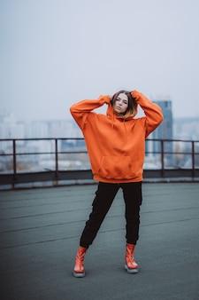 Jovem mulher com uma camiseta laranja posa no telhado de um edifício no centro da cidade