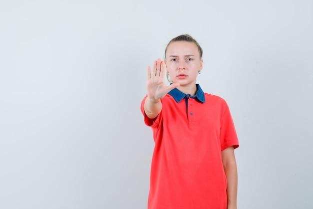 Jovem mulher com uma camiseta mostrando um gesto de pare e olhando séria