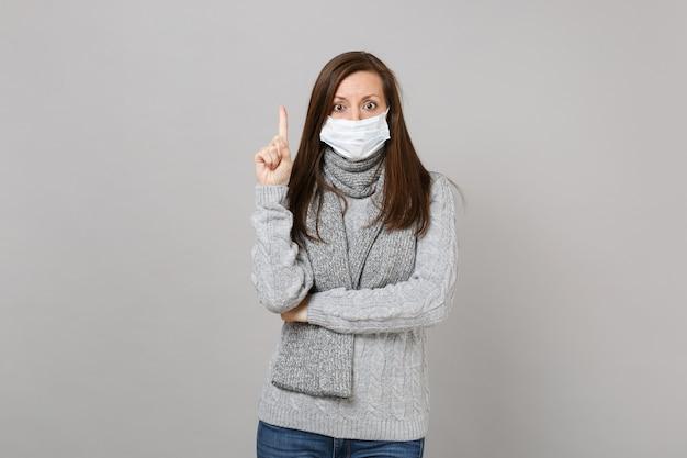 Jovem mulher com uma camisola cinza, lenço com máscara facial estéril, apontando o dedo indicador isolado no fundo cinza. estilo de vida saudável, tratamento de doença doente, conceito de estação fria. simule o espaço da cópia.