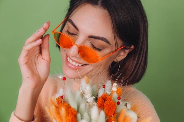 Jovem mulher com uma camisola pêssego casual isolada na parede verde-oliva segura uma composição de caixa de flores brancas e laranjas de flores de algodão, gipsófila, trigo e lagurus para um presente feliz surpresa