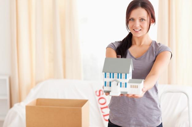 Jovem mulher com uma casa modelo olhando para a câmera