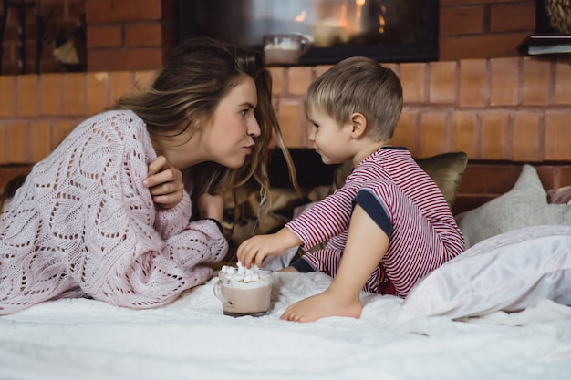 Jovem mulher com uma criança à beira da lareira. mãe e filho bebem cacau com marshmello perto da lareira.
