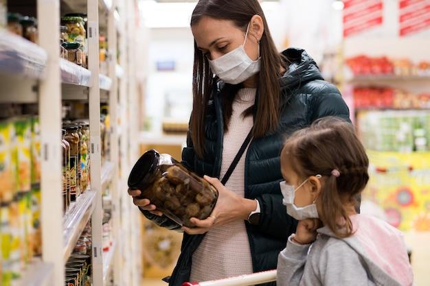 Jovem mulher com uma criança com máscaras médicas compra uma comida enlatada no departamento de mercearia a