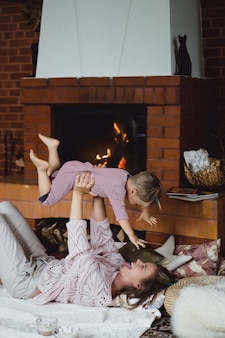 Jovem mulher com uma criança. mãe e filho estão brincando, se divertindo perto da lareira.