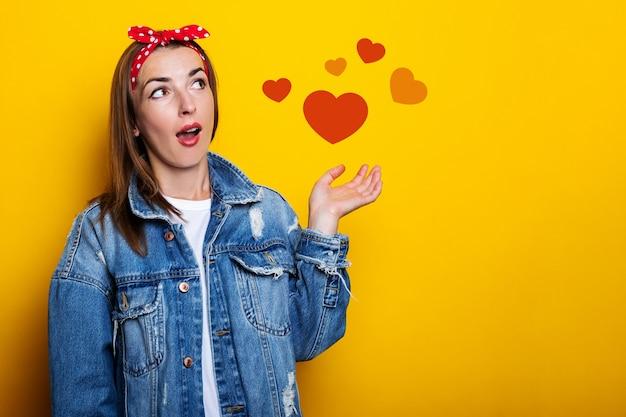Jovem mulher com uma faixa de cabelo, em uma jaqueta jeans, parece surpresa ao lado em uma parede amarela.