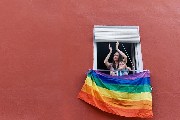 Jovem mulher com uma máscara batendo palmas da janela com a bandeira gay