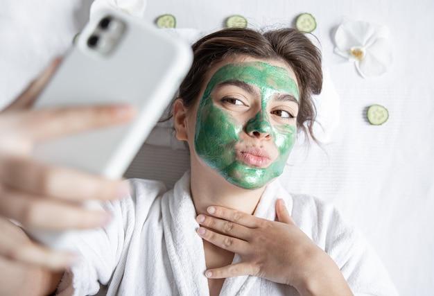 Jovem mulher com uma máscara cosmética no rosto faz uma selfie em um smartphone.